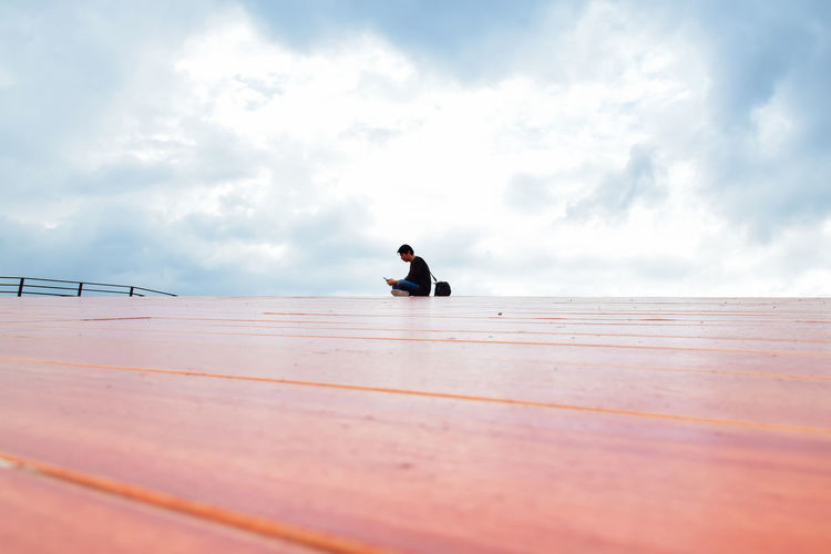 Man sitting on wooden railing against sky