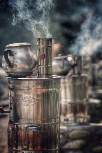Smoke coming out from glass by tea kettle on metallic container