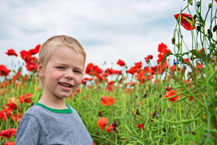 Portrait Of Smiling Boy Standing Against Red Poppy Flowers