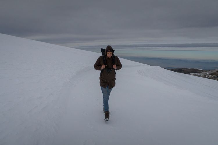 Man walking on snow covered landscape against sky