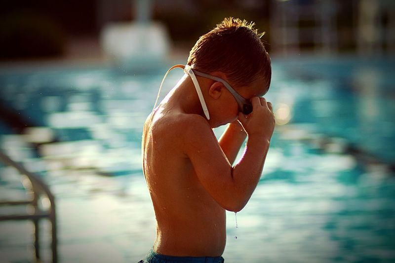 Side view of shirtless boy standing by swimming pool