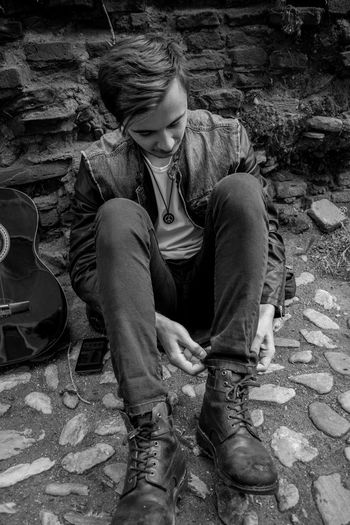 High angle view of young man adjusting jeans while sitting on cobbled street by guitar