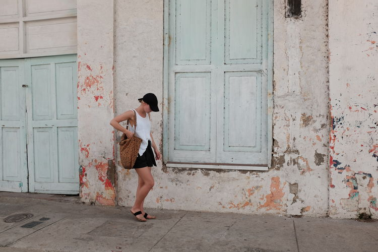 Side view of woman standing on footpath by weathered building