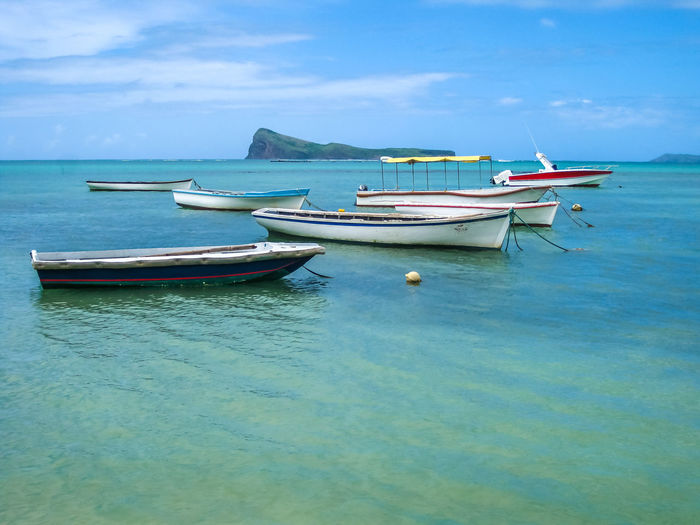 Fishing boats in Malheureux a small fishing village with a beautiful clear blue waters. Located at the northernmost tip of the country near Grand Baie and Pereybere. In the background, Coin de Mire. Mauritius Mauritius Island  Island Africa Gris Gris Coast Gris Coast Ocean Sea Beach Fish Fishing Fishing Boat Nature Cliffs Seascape Fisherman Belle Mare Belle Mare Plage Plage Plage 🌴 Indian Ocean Trou Aux Biches Waterfront Moored Nautical Vessel Water Transportation Mode Of Transportation Sky Blue Day Cloud - Sky Beauty In Nature No People Scenics - Nature Tranquility Horizon Over Water Travel Tranquil Scene Outdoors Anchored Rowboat Turquoise Colored