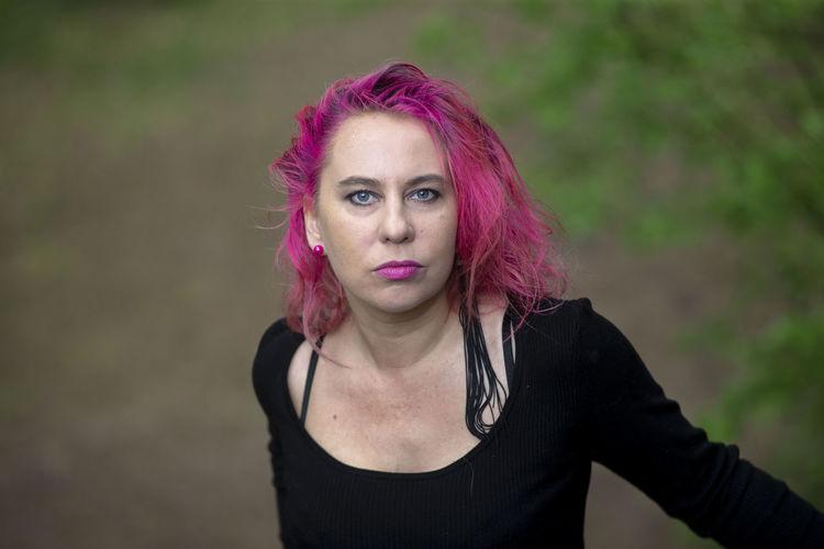 Portrait of beautiful woman against purple outdoors