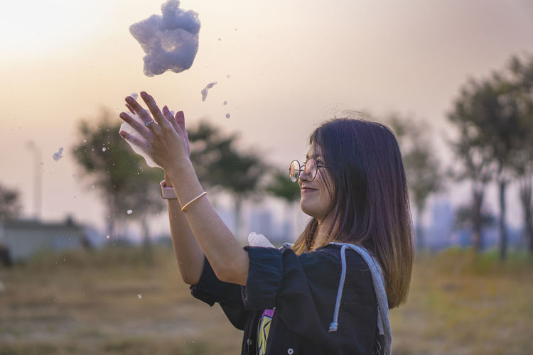 Young woman playing with soap sud during sunset