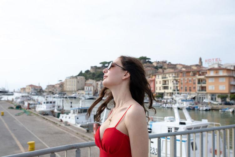 Side view of woman standing on footbridge at harbor