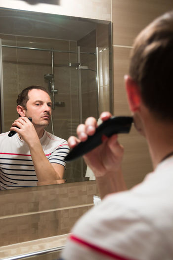 Young man reflecting on mirror while trimming beard in bathroom