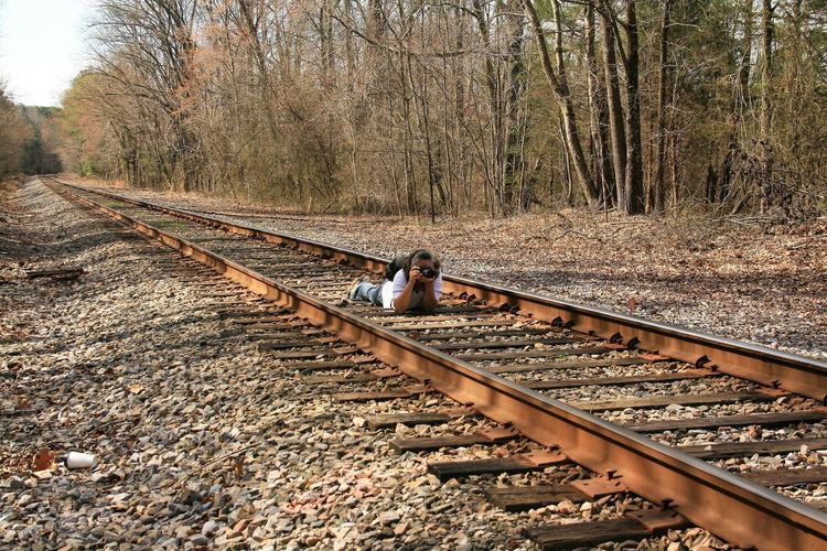 Mature woman photographing while lying on railroad tracks in forest