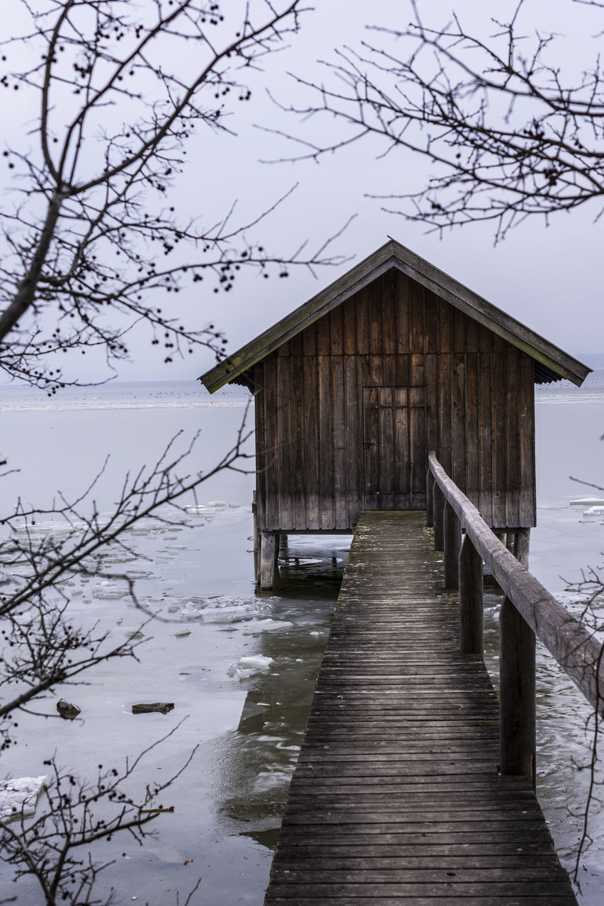built structure, architecture, wood - material, water, nature, building exterior, no people, tree, tranquility, cold temperature, sky, day, snow, winter, tranquil scene, house, lake, building, outdoors