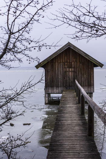 A wooden bridge to a boat house on a frozen lake in bavaria germany Ammersee Water Nature Lake Covered Bridge Beauty In Nature Architecture Outdoors Horizon Over Water Wood - Material Minimalist Architecture Freeze Winter Background Texture Pattern Poster Poster Art ARTsbyXD EyeEm Nature Lover Landscape Nature EyeEm Gallery Boat House Scenics