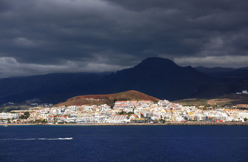 Sea And Community By Mountains Against Cloudy Sky
