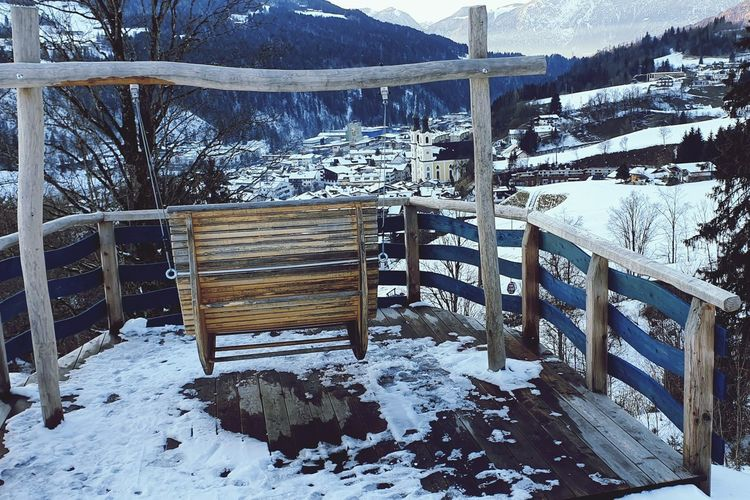 Snow covered bench against mountain