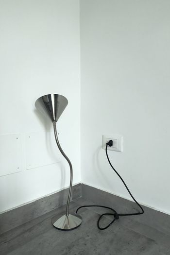 Electric lamp on table against white wall