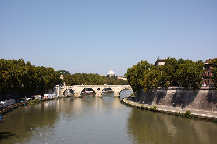 Arch bridge over tiber river against clear sky