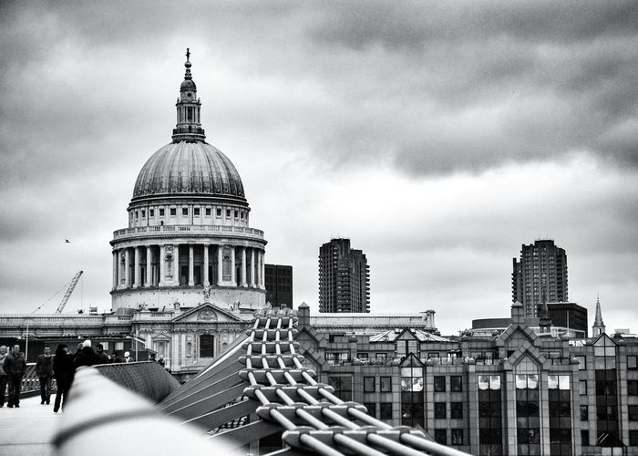 Millennium bridge with st paul cathedral against cloudy sky