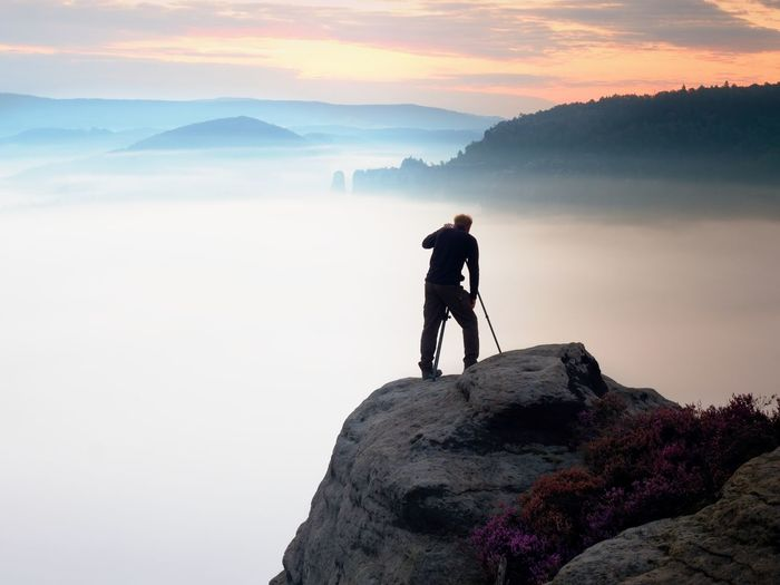 Professional photographer takes photos with mirror camera and tripod on peak of rock. misty  valley