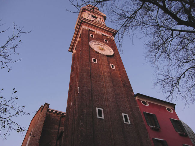Clock tower at Santi Apostoli church in Venice, Italy Apostoli Architecture Brick Brickwork  Church City Clock Clockface Cross Famous History Italy Landmark Numbers Numerals Religion Santi Sunset Tall Time Timepiece Tourism Tower Venezia Venice