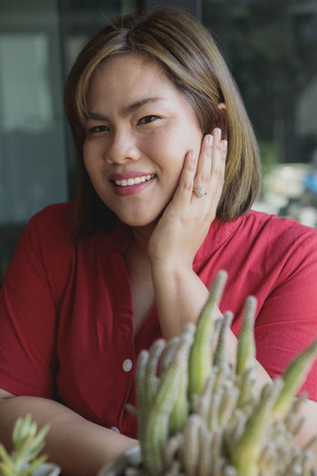 Portrait of smiling woman sitting by succulent plant on table