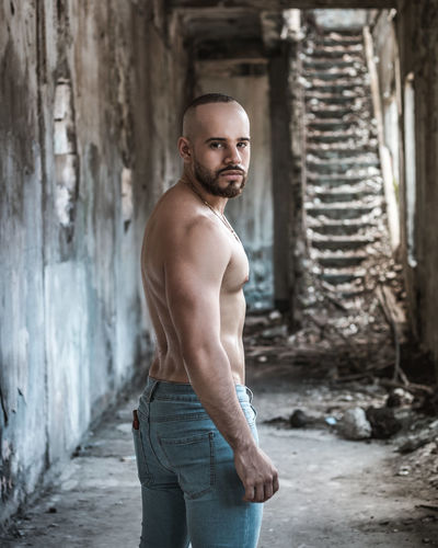 Portrait Of Shirtless Man Standing In Abandoned Building