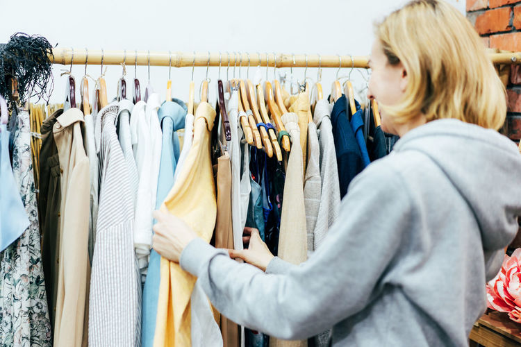 Woman shopper chooses fashionable clothes on hangers in a boutique.