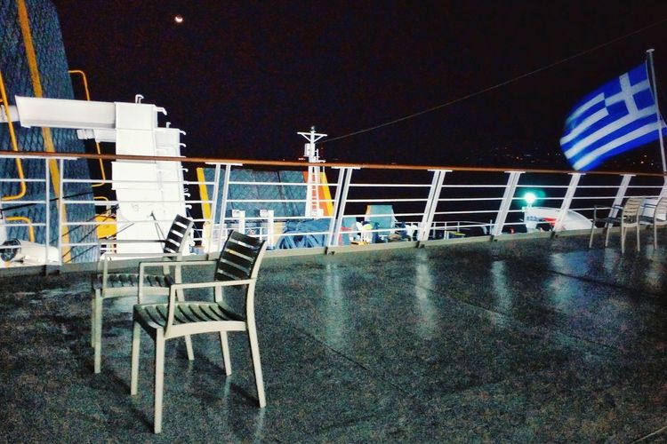 A ship and two plastic chairs; national pride Chair Night No People Mobile Photography Snapseed Nightphotography Nightshot On The Ferry On Deck Flags In The Wind  Greek Flag On The Ship Flag On A Ship Plastic Chair