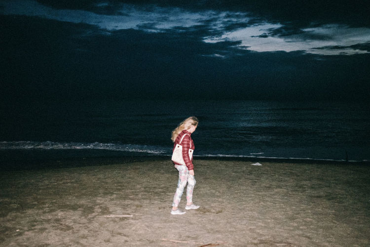 Girl standing on beach against sea