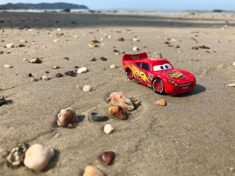 Port Dickson, Malaysia - March 23, 2017: A Lightning McQueen Toy Car at Port Dickson beach. Lightning McQueen is the main character from the popular Disney movie Cars. Merchandise from movies are very popular with children and collectors worldwide. Beach Toy Toy Car Outdoors Disney Pixar  Lightning Mcqueen