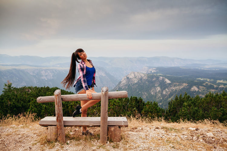 Portrait of woman standing on mountain by bench against sky