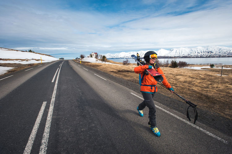 Woman running on road against sky during winter