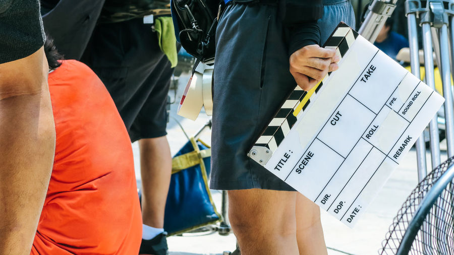 Midsection of man standing with film slate by people