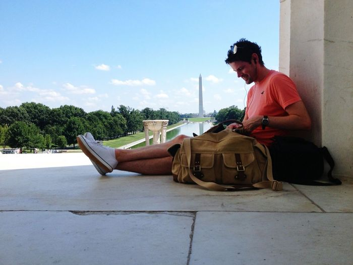 Man Relaxing Against View Of Washington Monument