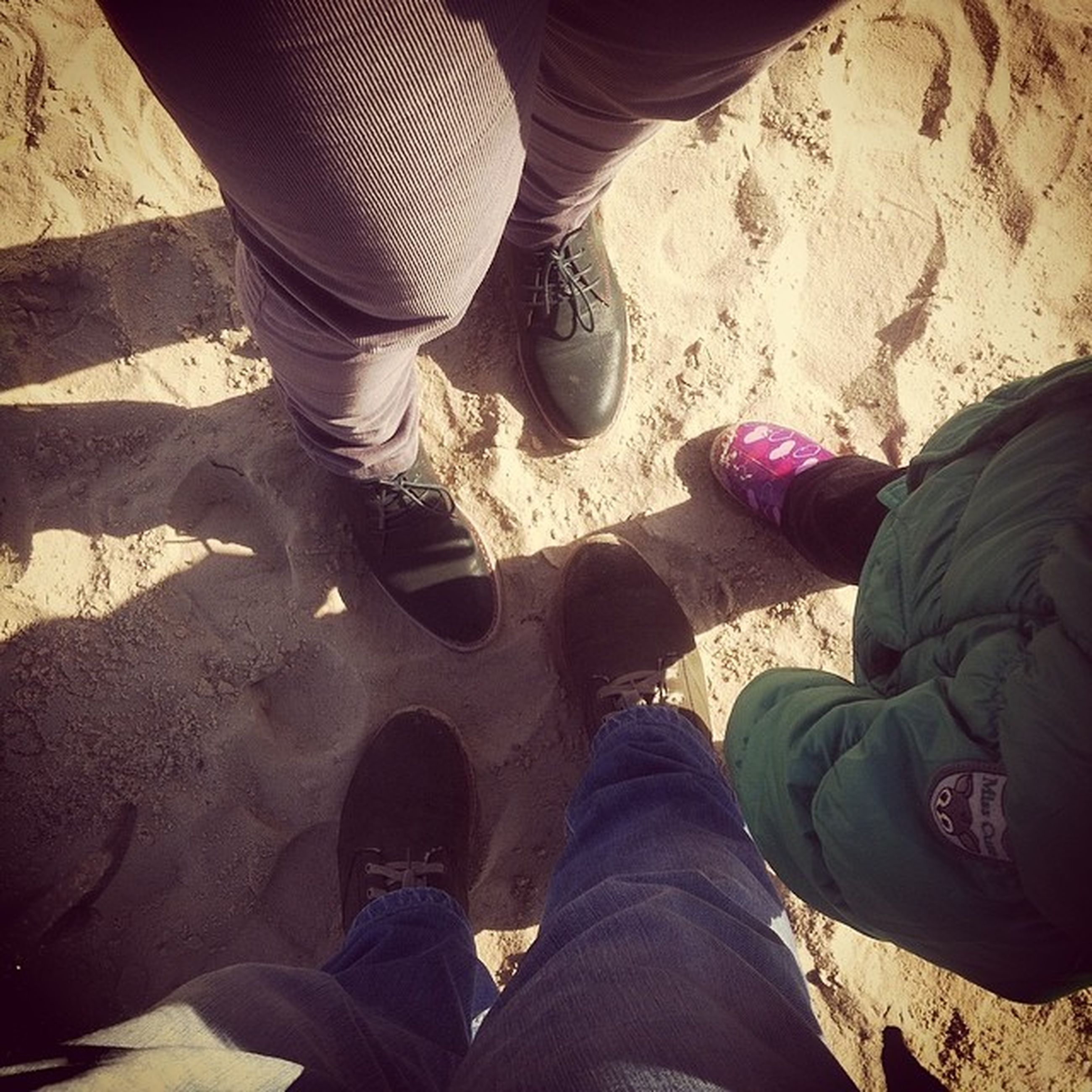 low section, person, shoe, lifestyles, men, standing, leisure activity, togetherness, jeans, human foot, casual clothing, personal perspective, high angle view, bonding, footwear, friendship, sand