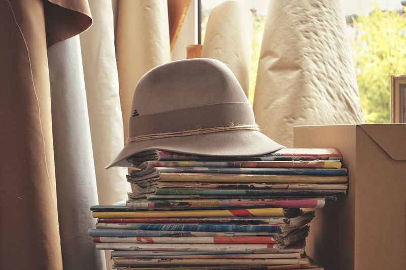 Close-up of hat on stacked book