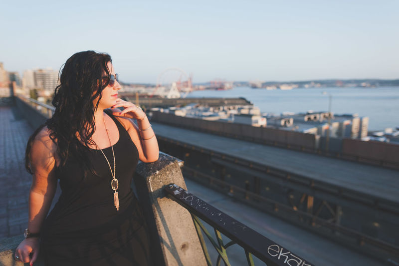 Thoughtful woman leaning on railing against sky