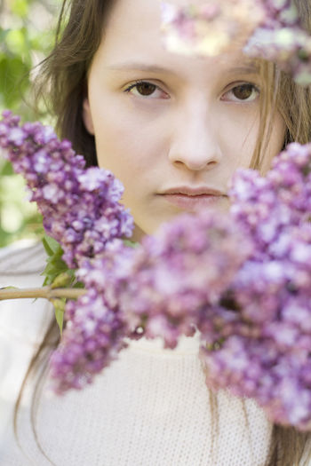 Beautiful Woman Beauty In Nature Close-up Flower Flower Head Flowering Plant Fragility Freshness Front View Hairstyle Headshot Human Face Leisure Activity Lifestyles Lilac Looking At Camera Nature One Person Outdoors Plant Portrait Purple Real People Spring Flowers Women