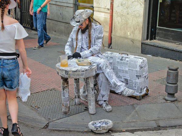 Street performer with a costume made of newspapers, next to a table and suitcase also wrapped in newspaper, on the Madrid 'El Rastro' flea market. Dressed Up El Rastro Hat Madrid SPAIN Suit Busker Buskers Busking Day El Retiro Fleamarket Lifestyles Men Newspaper Outdoors Pavement Real People Street Theatre Suitcase Suits