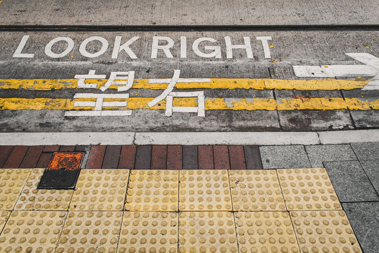 """English and Chinese """"look right"""" sign on a street in hong kong, advising safety for pedestrians. Sign Look Hong Kong Street Road Road Sign Right Crossing Sign City Pedestrian Pedestrian Crossing Sign Pedestrian Walkway Traffic Urban Symbol Directional Sign Direction Asphalt Asphalt Road Safety Warning Warning Sign Zebra Crossing Text Drive"""