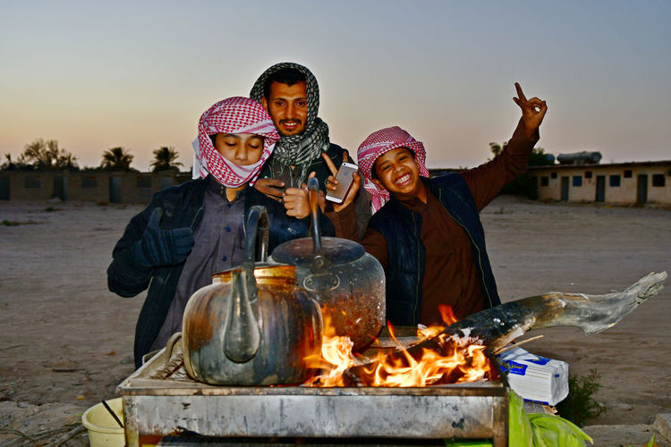 Happy Arabic boys with head scarfs are enjoying making coffee on street stand in coffee pots with burning wood on fire and flames Flames Friends Happiness Adult Adults Only Day Enjoying Life Enjoying Life With Friends Fire Flames Burning Flames Of Fire Friendship Men Outdoors People Portrait Real People Sky Smiling Smiling Face Sunset Together Togethre Young Adult Young Women