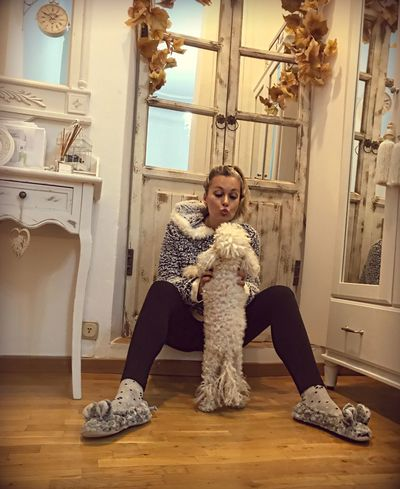 Playing Friendship Loyalty Togetherness Bonding Confidence  Conection Poodletoy Poodle Dog Indoors  Full Length One Person Real People Sitting Young Adult Elementary Age Looking At Camera Portrait Home Interior Lifestyles Casual Clothing Leisure Activity Corridor Childhood Smiling Happiness