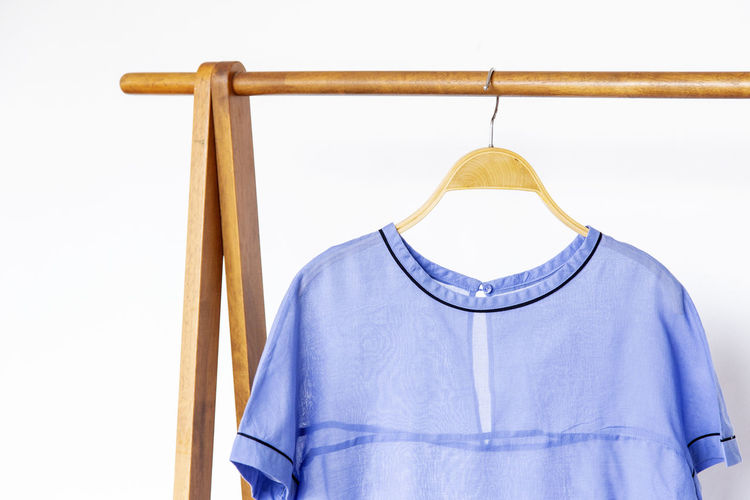 Woman blouse with blue blouse cotton on wooden hangers. Hanging Coathanger Clothing Indoors  White Background No People Studio Shot Wood - Material Blue Casual Clothing Still Life Wall - Building Feature Fashion Textile White Color Cut Out Two Objects Close-up T-shirt Dress Coat Hook Garment Blouse Hanger Wood Handmade Craft