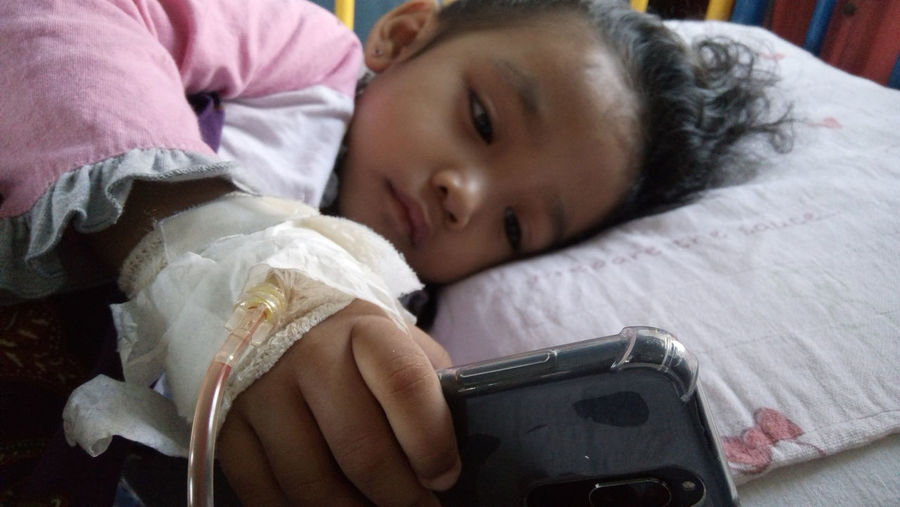 Cute injured girl using phone while lying on hospital bed