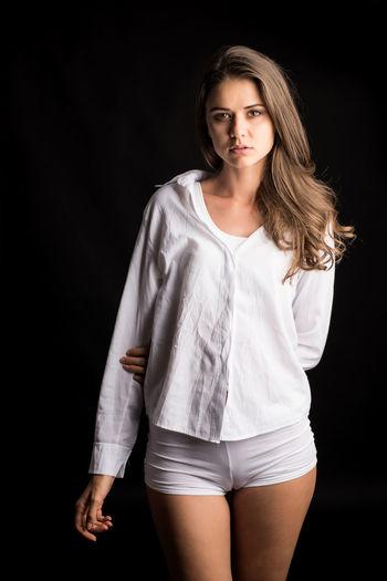 Portrait Looking At Camera Three Quarter Length Young Adult One Person Front View Studio Shot Young Women Black Background Women Standing Beauty Casual Clothing Hair Indoors  Beautiful Woman Long Hair Lifestyles Hairstyle Fashion Shorts