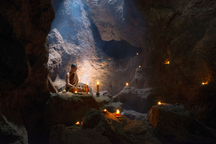 Buddha Novice or priest is praying in a cave with candles and date is 15 June 2018, Cave in Wat or temple in Sangkom sub district, Nongkai, Thailand ASIA Asian  Believer Buddha Buddhist Cambodia Candle Faith Thai Thailand That's Me Buddism Cave Culture Editorial  Faithful Monastic Monk  Mynmar Novice Prayer Praying Priest Religion Religious