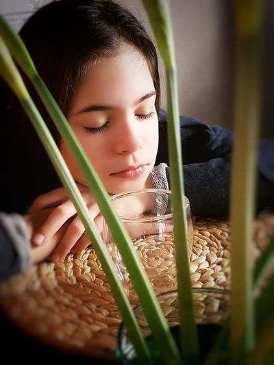 Close-up of girl wits eyes closed by empty drinking glass