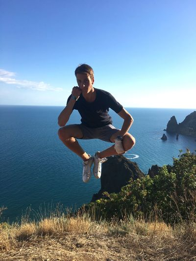 Full Length Of Young Man Levitating Over Cliff Against Sea And Sky