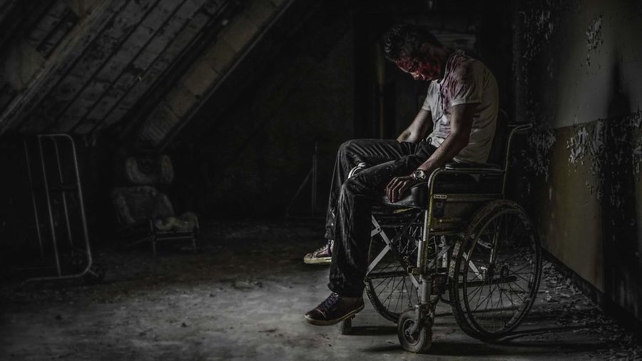 Side view of a young man sitting in abandoned room