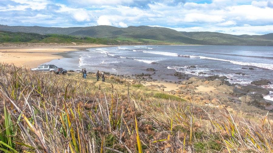Scenic view at Cloudy Bay Bruny Island Tasmania Tourist Attraction  Algae Beach Beauty In Nature Bruny Island Tasmania Cloud - Sky Day Environment Grass Holiday In Tasmania Idyllic Land Mountain Nature Non-urban Scene Outdoors Plant Purple Sea Rocky Beach Scenics - Nature Sea Sky Tranquil Scene Tranquility Water