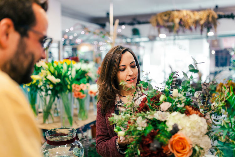 Rear view of man with woman holding bouquet at store