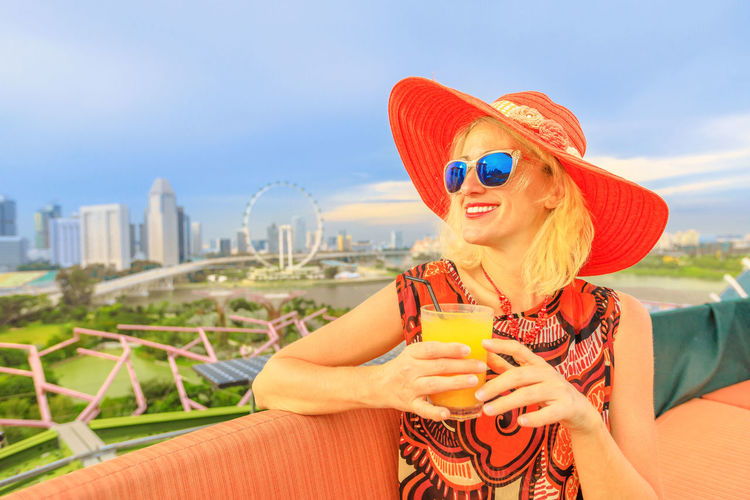 Lifestyle caucasian woman with alcoholic cocktail, drinking aperitif at rooftop. Aerial view or cityscape skyline. Holiday vacation in Singapore, Southeast Asia. Singapore Singapore City Woman Tourist Tourist Attraction  Tourist Destination People Girl Females Aerial View Skyline Cityscape Panorama Happy Travel Hat Lifestyle Enjoy Nature Tourism Smiling Aperitif Drink Orange Juice  Analcolic Glass Leisure Activity Glasses Real People One Person Sunglasses Architecture Sky Fashion Holding Food And Drink Adult Refreshment Lifestyles Casual Clothing Young Adult Portrait Drinking Outdoors Wireless Technology Cocktail